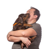 Adult man is holding his sweet puppy isolated on white backgroun — Stock Photo