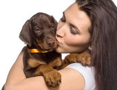 Brunette girl kissing her puppy isolated on white background — Stock Photo