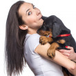 Brunette girl biting her doberman puppy by ear — Stock Photo