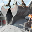 Crane loading cargo ship with gravel - Stock Photo