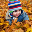 Baby boy in autumn leaves — Stockfoto