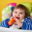 Baby boy eating carrot - Stock Photo