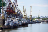 River docks with cranes and ships. — Stock Photo