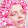 Beautiful woman with pink flowers on head — Stock Photo