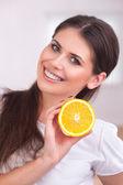 Beautiful girl with juicy orange — Stock Photo