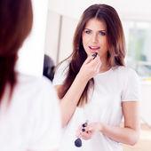 портрет положить макияж, сексуальная девушка смотрит в зеркало — Стоковое фото