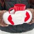 Hands in mittens with hearts holding cup — Stock Photo