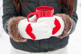 Hands in mittens with hearts holding cup — Stockfoto