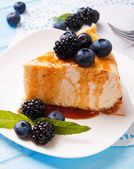 A piece of cheesecake with caramel and berries — Stock Photo