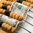 Dollar banknote in wooden abacus — Stock Photo #27829785