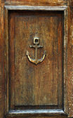 Anchor on old wooden door — Stock Photo