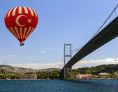 Hot air balloon flying Bosphorus bridge — Stock Photo