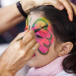 Little girl having face painted on party — Stock Photo
