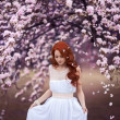 Beautiful young woman under the flowering tree — Stock Photo