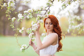 Beautiful woman in the flowering park — Stock Photo