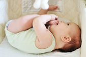 Baby with feet in mouth — Stock Photo