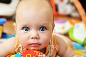 Blue-eyed baby with toys — Stock Photo