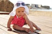 Tanned baby girl on the beach — Stock Photo