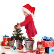 Little santa helper decorating a tree — Stock Photo