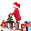 Little santa helper decorating a tree - Stock Photo