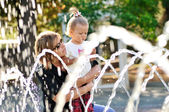 Mother and daughter playing with fountain — Stock Photo