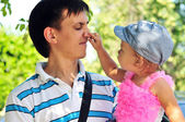 Baby girl showing father's nose — Stock Photo