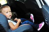 Cute girl in car seat — Stockfoto