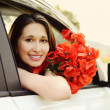 Stock Photo: Girl in car with flowers
