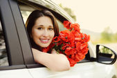 Girl in car with flowers — Stock Photo