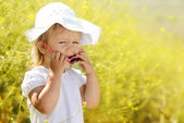 Laughing toddler in rape field — Stockfoto