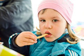 Girl eating french fries — Stock Photo
