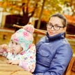Mother with baby daughter in autumn park — Stock Photo