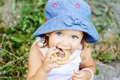 Toddler girl eating cracknel — Stock Photo