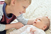 Brother glad to see baby sister — Stock Photo