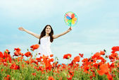 Happy girl with windmill in field — Stock Photo