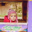 Baby girl in wooden house — Stock Photo