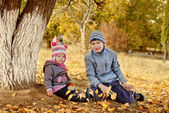 Brother and sister playing leaves in park — Stock Photo