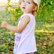 Toddler girl in green garden — Stock Photo