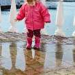 Stock Photo: Baby girl walking in puddle