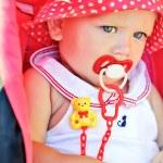 Baby girl sitting in red stroller — Stock Photo #46513589