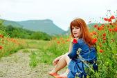 Redhead girl in poppy field — Stock Photo