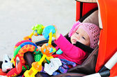 Baby in stroller  with toys — Stock Photo