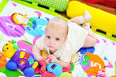 Baby on carpet with toys — Stock Photo