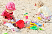 Babies playing toys in sand — Stock Photo