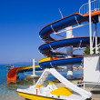 Waterslide and catamaran on beach - Stock Photo