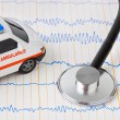 Stethoscope and ambulance car on ecg - Stock Photo