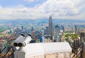 Binoculars and Kuala Lumpur (Malaysia) city view — Stock Photo