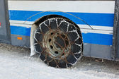 Snow winter chains on tyre of car — Stock Photo