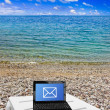 Netbook on beach - Stock Photo