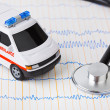Stethoscope and ambulance car on ecg — Stock Photo